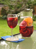 Sangria. Glass and pitcher of red wine sangria on outside backyard dining table stock images