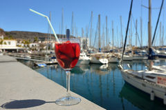 Sangria. Full glass of sangria against marina of Puerto de Mogan. Gran Canaria, Spain stock image