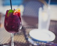 Sangria glass with white plate and water cup in background royalty free stock image