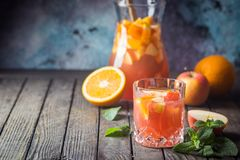 Sangria or punch with fruits. Refreshing summer drink sangria or punch with fruits in a glass and pincher over wooden background royalty free stock images