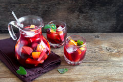 Sangria. Red wine sangria or punch with fruits and ice in glasses and pincher. Homemade refreshing fruit sangria over rustic wooden table, copy space royalty free stock photos