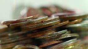 Sangue che droping attraverso le monete in vetro stock footage