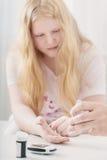 Sangue de medição Sugar Level Of Teen Girl com Glucometer imagens de stock royalty free