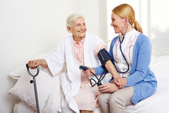 Sangue di misurazione dell'infermiere geriatrico Fotografie Stock Libere da Diritti