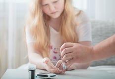 Sangue di misurazione Sugar Level Of Girl With Glucometer fotografie stock libere da diritti