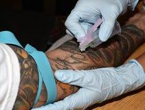 Sangue do desenho de um braço tattooed Imagem de Stock