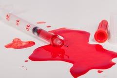 Sangue vermelho esguinchando da seringa no fundo branco Imagem de Stock