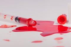 Sangue vermelho esguinchando da seringa no fundo branco Fotografia de Stock Royalty Free