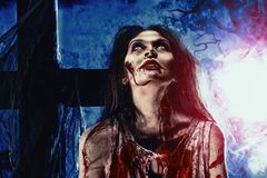 Sanguinary. Bloodthirsty zombie standing at the night cemetery in the mist and moonlight Stock Photos