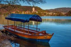 Sanguinato, la Slovenia - la barca blu tradizionale di Pletna nel lago ha sanguinato con la chiesa di pellegrinaggio del presuppo Fotografie Stock