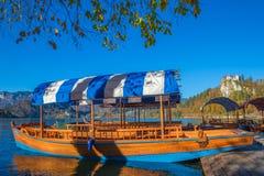 Sanguinato, la Slovenia - la barca blu tradizionale di Pletna nel sole di autunno nel lago ha sanguinato Fotografie Stock Libere da Diritti