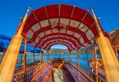 Sanguinato, la Slovenia - la barca rossa tradizionale di Pletna nel lago ha sanguinato un giorno soleggiato di autunno Fotografia Stock