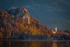 Sanguinato, la Slovenia - la bella alba di autunno nel lago ha sanguinato con il castello e la chiesa sanguinati Fotografie Stock
