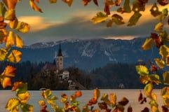 Sanguinato, la Slovenia - il bello tramonto di autunno nel lago ha sanguinato con la chiesa famosa di pellegrinaggio del presuppo Fotografia Stock Libera da Diritti
