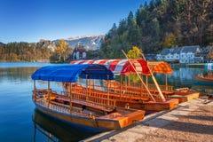 Sanguinato, la Slovenia - le barche rosse, arancio e blu tradizionali di Pletna nel sole di autunno nel lago hanno sanguinato Immagine Stock Libera da Diritti