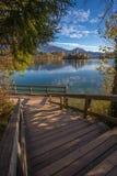 Sanguinato, la Slovenia - le scale ed il pilastro di legno nel bello lago hanno sanguinato con la chiesa famosa di pellegrinaggio Fotografia Stock