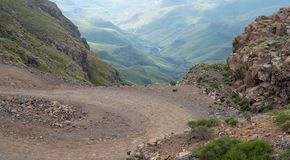 View of the Sani Pass, winding dirt rural road though the mountains which connects South Africa and Lesotho. The Sani Pass, winding dirt road through the royalty free stock photo