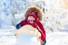 Sania i śniegu zabawa dla dzieciaków Dziecko sledding w zima parku Obrazy Royalty Free