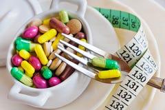 Sanità e benessere - sia a dieta le pillole e peso allentare - varie compresse in un vaso con le forcelle Immagini Stock