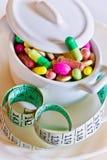 Sanità e benessere - sia a dieta le pillole e peso allentare - varie compresse in un vaso con il metro di misurazione Fotografie Stock