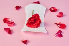 Sanitär servett och blomma på rosa bakgrund arkivbild