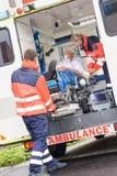 Sanitäter, die Patienten in Krankenwagenautohilfsmittel einsetzen stockbild