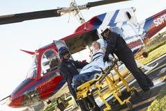 Sanitäter, die Patienten vom Hubschrauber aus dem Programm nehmen Stockbild