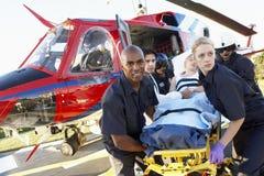 Sanitäter, die Patienten vom Hubschrauber aus dem Programm nehmen Lizenzfreie Stockfotos