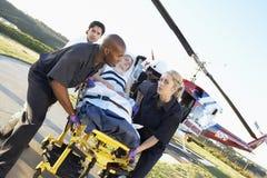Sanitäter, die Patienten vom Hubschrauber aus dem Programm nehmen stockfotografie