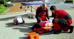 Sanitäter, die verletztes Mädchen auf ein Rückenbrett setzen stock video footage