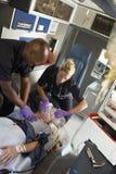 Sanitäter mit Patienten im Krankenwagen Stockbilder