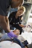 Sanitäter mit Patienten im Krankenwagen Stockbild