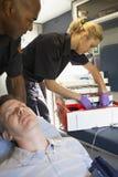 Sanitäter mit Patienten im Krankenwagen Lizenzfreie Stockbilder