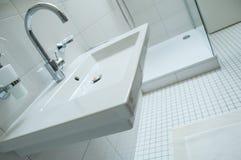 Sanitarny z chromium faucet i białą łazienką z obrazy stock