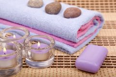 Sanitary articles. Stones and the lit candles in candlesticks Stock Photography