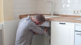 Sanitary engineering repair of water leakage. man fixing a faucet in the kitchen