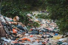 Sanitary landfill inside forest - garbage dump, waste desposit -. Environmental pollution Stock Photo