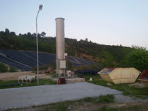 Sanitary landfill with utilities. View of a sanitary landfill including a biogas flare, hdpe pipes, a skip container and the cell covered with Geo-textile Royalty Free Stock Photos