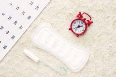 Sanitary menstruation pad for woman menstrual period. Red clock. Sanitary menstruation pad for woman menstrual period. an overhead photo royalty free stock photography
