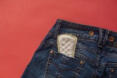 Sanitary napkin in back of pocket blue jeans. Women health, menstruation or period days. Concept stock image