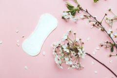 The sanitary napkin lying with blossom on pink background.  stock photography