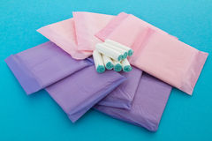 Sanitary napkins and tampons. On blue background Royalty Free Stock Photography