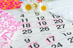 Sanitary pads, calendar, towel and pink flower on light background royalty free stock images