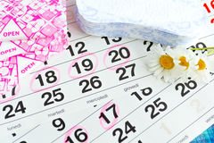 Sanitary pads, calendar, towel and pink flower on light background royalty free stock photos