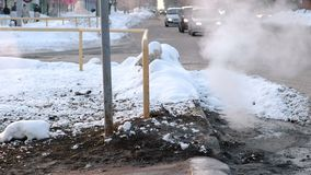 Sanitary sewer cover in snow with steam, accident. Side view.
