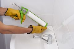 Sanitary silicone sealant. Plumber fills the seam between the sink and the tile with a silicone sealant Royalty Free Stock Image