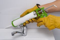 Sanitary silicone sealant. Plumber fills the seam between the sink and the tile with a silicone sealant Stock Photo