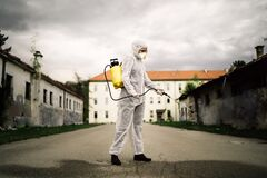 Sanitation service worker disinfecting public space with disinfectant spray.Street disinfection.Coronavirus COVID-19 pandemic