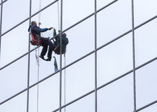Sanitation worker cleaning glass facade hotel Stock Photos