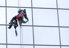Sanitation worker cleaning glass facade hotel Stock Image